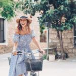 kobieta w sukience z opadającymi ramionami na rowerze